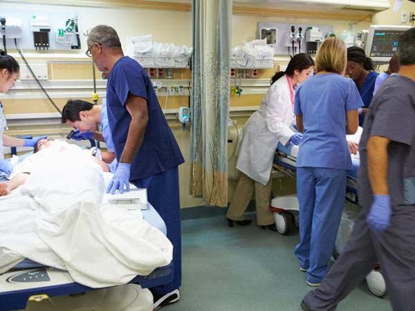 Doctors attend to multiple patients in emergency room.