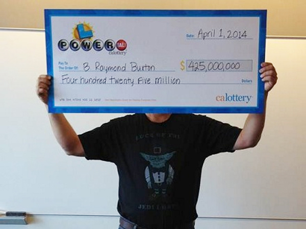 "No April Fool´s joke: Powerball winner B. Raymond Buxton holding a ceremonial check for $425 million, the amount of the annuity jackpot he hit in February 2014. Buxton´s shirt had a picture of Yoda with the message ""Luck of the Jedi I have."" (California Lottery)"