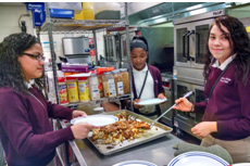 Paola Rodriguezm Taniyah Waples, and Melany Morales prepare curried chicken with cauliflower, olives and apricots during week 7 of My Daughter's Kitchen at Camden Promise Charter School.