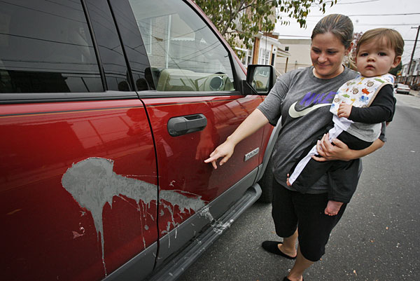 Jaine Kromchad, with son Nicholas, is one of many residents around Second and Wolf that had their cars vandalized overnight. Her Ford Explorer was damaged by acid on the passenger side. (ALEJANDRO A. ALVAREZ / Staff Photographer)