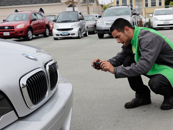 Brendon Bucini takes of photo of prior damage of a car that will be rented at FlightCar in Millbrae, California, August 7, 2013. FlightCar is a car-sharing service that allows travelers to leave their cars in a parking lot so that others can rent it while they are gone. (Gary Reyes/Bay Area News Group/MCT)