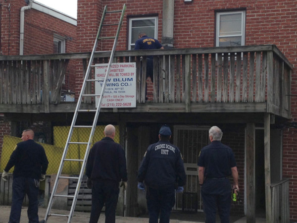 Police investigate the site of a May 6, 2013 home invasion on Castor Ave. in Northeast Philly that left a 74-year-old woman dead and a man hospitalized. (Emily Babay/ Staff)