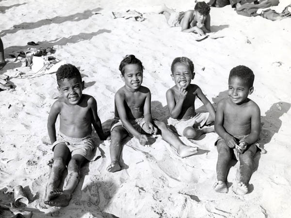 """Children in the sand at """"Chicken Bone Beach,"""" a photograph by John W. Mosley displayed in the Chicken Bone Beach exhibit at Art Sanctuary Gallery from May 1 through May 31."""