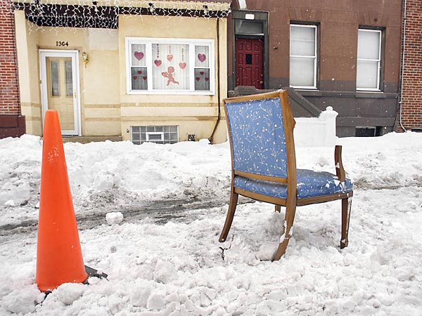 """Parking spots on Ellsworth Street between 13th and Broad are  """"reserved"""" with a pylon and a chair on Wednesday, Feb. 18, 2014. (Eric Mencher/Staff)"""