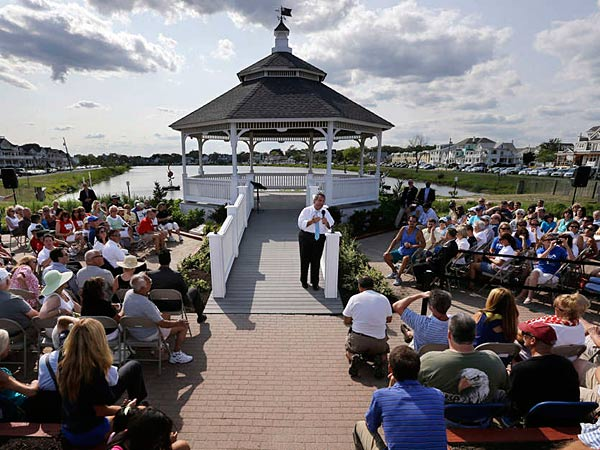"""Gov. Christie continued his Shore talks with a town-hall meeting Wednesday at a gazebo near Belmar´s beach. The crowd included many retired teachers and other state workers who held signs and wore shirts that said """"Our Pain, Christie´s Gain"""" - a play on the """"No Pain, No Gain"""" title his staff has given this summer´s push. (Mel Evans/AP)"""