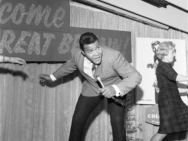 "Chubby Checker, the 20-year-old entertainer from Philadelphia who started the ""Twist"" craze, pictured dancing during a press reception in London, England on Dec. 14, 1961. Chubby is in London for radio and television appearances. (AP Photo)"
