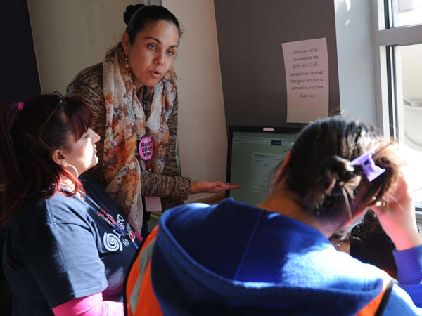At Congreso Education & Training Center in North Philadelphia, application counselor Elizabeth Rosario (standing) helps a woman (right) who wants to apply for health-care coverage online. The group serves 14,000 people in the city´s Latino community.
