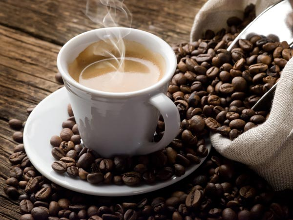 Smoking hot coffee with coffee beans.