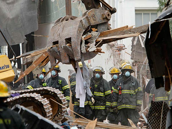 Firefighters watch as a backhoe removes debris from within the collapsed building.