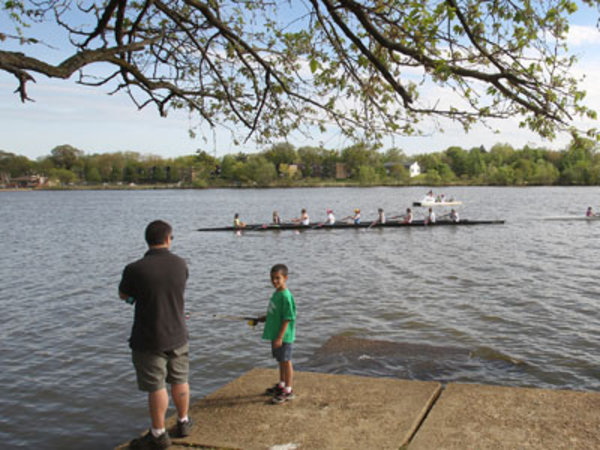 A young boy fishes while crew teams practice on the Cooper River at Cooper River Park in 2012. ( Charles Fox / Staff Photographer )