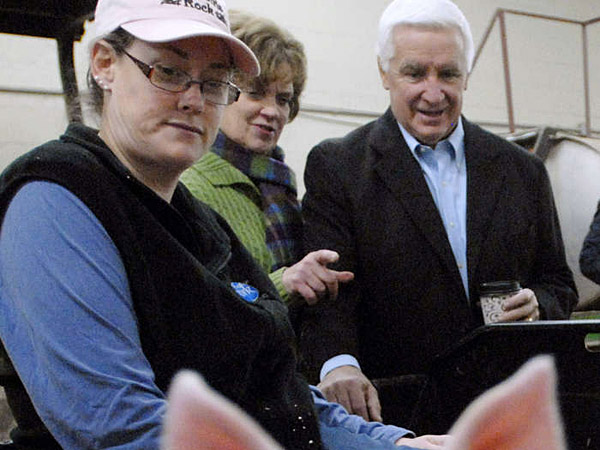 Gov. Corbett and wife Susan meet farmer Amy Bradford (left) and some of her piglets Saturday at the Farm Show. (Associated Press)