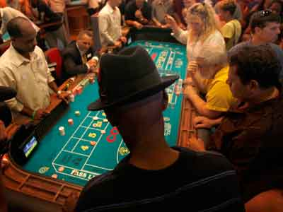 Customers gather around one of the craps table inside SugarHouse Casino. ( David Maialetti / Staff Photographer )