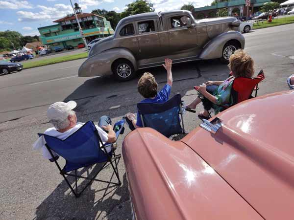 From left, Gary Frenkel watches as a custom vehicle drives past along Woodward Avenue in Royal Oak, Mich. while sitting with his sister-in-law, Benny Avig and his wife, Candy Frenkel, as they sit in front of Candy's 1957 Chevy convertible during the 2014 Woodward Dream Cruise on Thursday August 14, 2014.(Ryan Garza/Detroit Free Press/MCT)