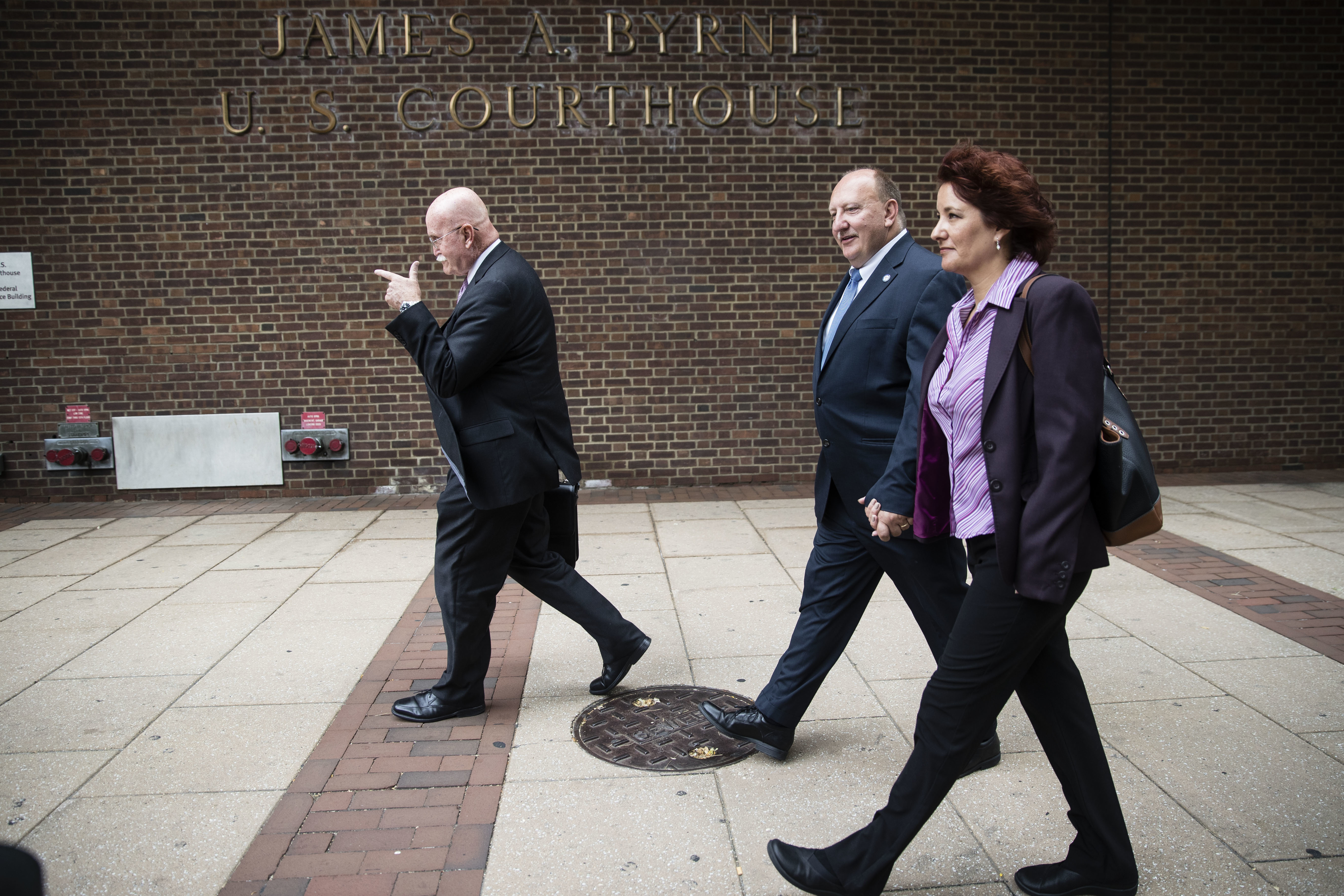 Allentown Mayor Ed Pawlowski, center, accompanied by his wife Lisa and lawyer Jack McMahon walk by the U.S. Courthouse in Philadelphia on July 27, 2017.