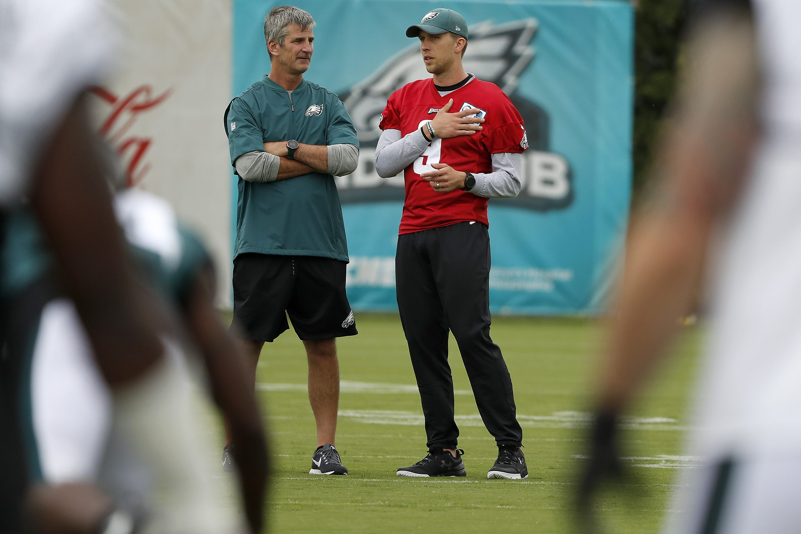 Eagles offensive coordinator Frank Reich talks with Nick Foles during Saturday´s workout. Foles sat out again on Sunday.