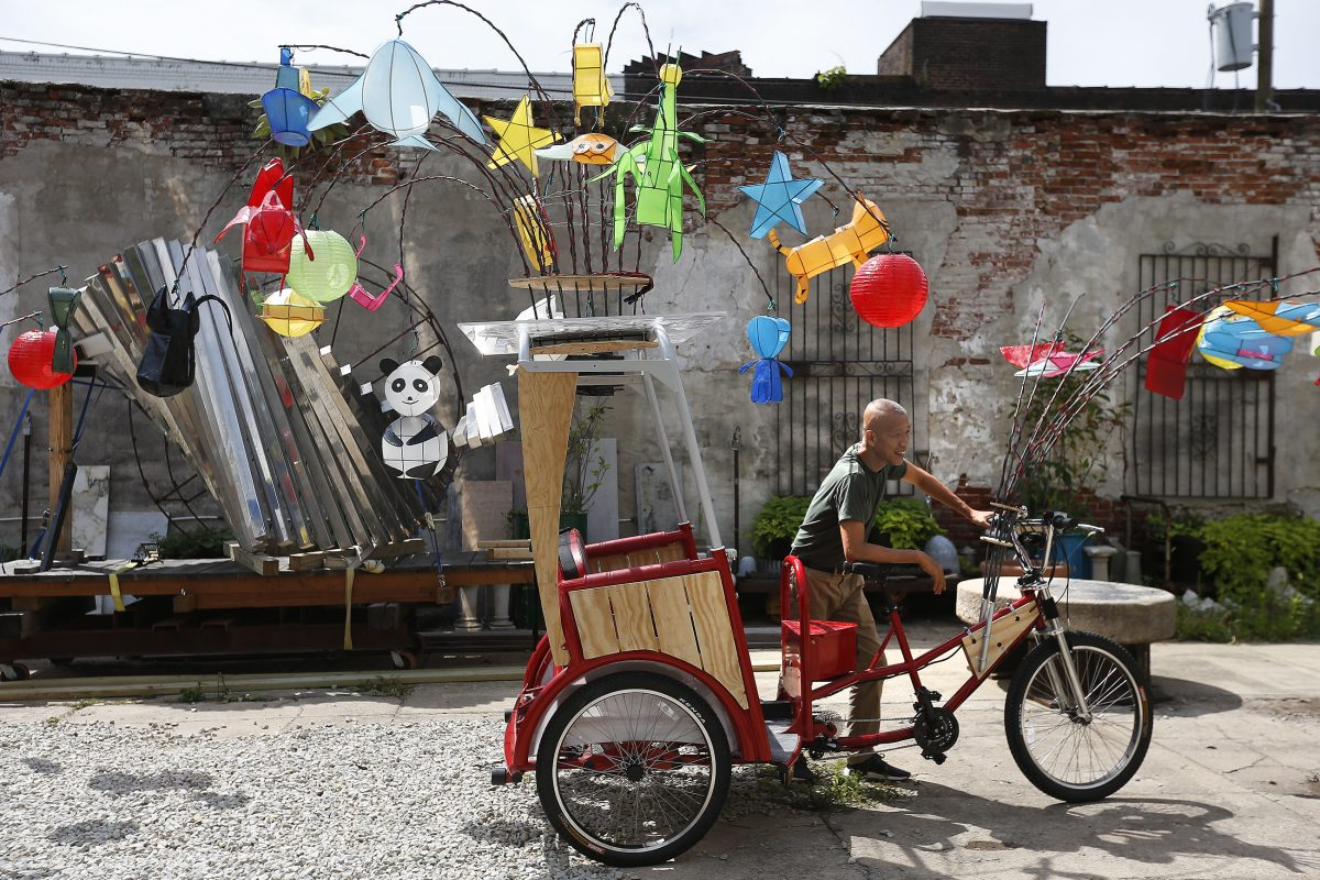 "Artist Cai Guo-Qiang with one of his ""Fireflies,"" a pedicab illuminated with lanterns that will be used in a monthlong public art performance celebrating the Benjamin Franklin Parkway'd centennial beginning in September."