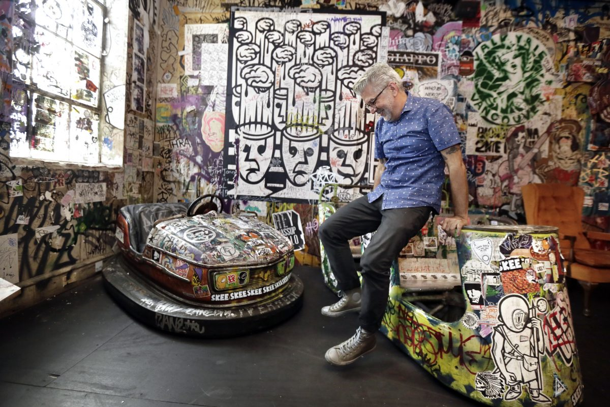 Tattooed Mom owner Robert Perry jumps from one amusement car to another in the upstairs street art gallery at the Tattooed Mom.