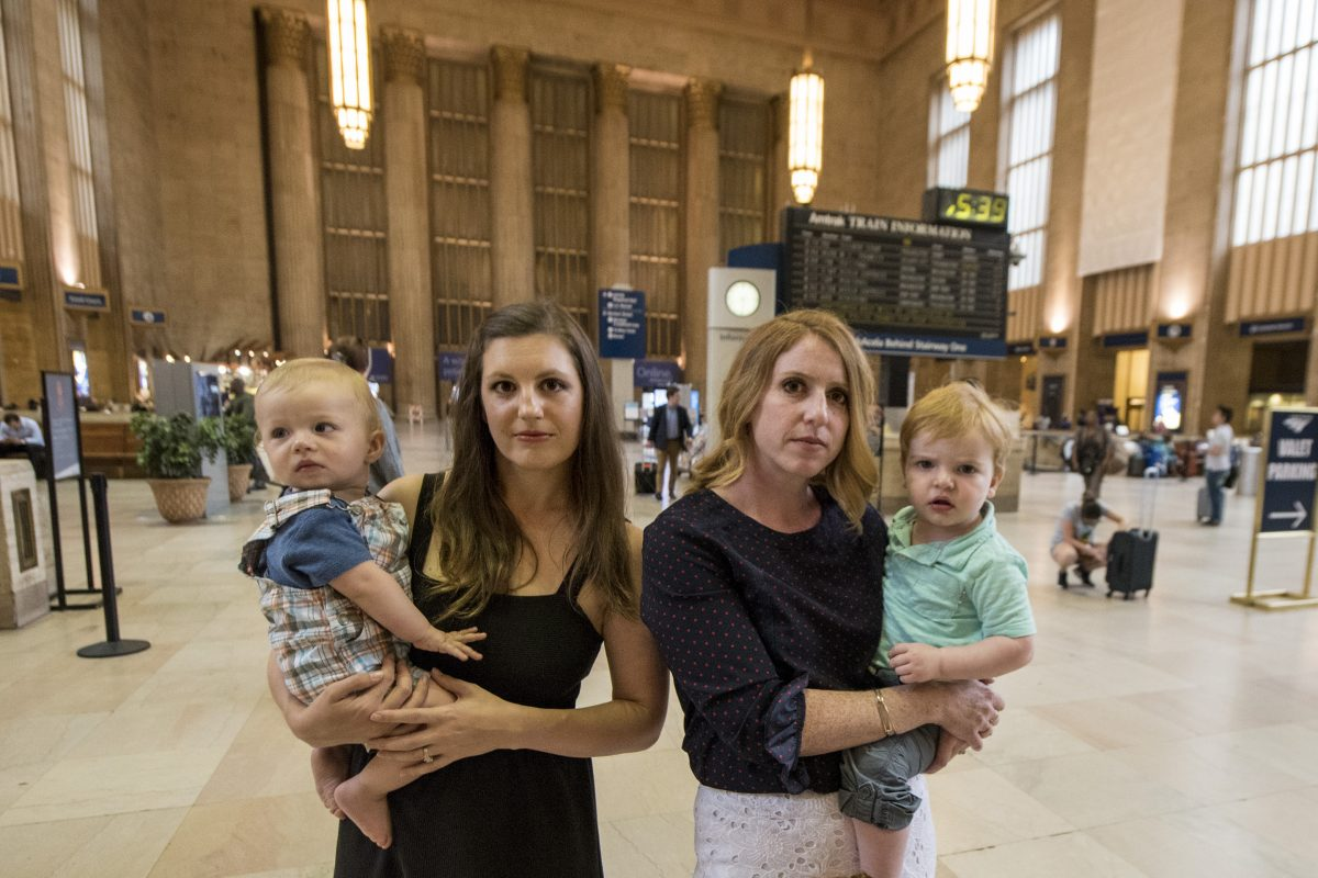 Lacey Kohlmoos (left), 34, holding 9-month-old Finn Heckert, and Samantha Matlin, 36, holding Logan Matlin, 21-month-old, in Amtrak's 30th Street Station on Tuesday.  CLEM MURRAY / Staff Photographer