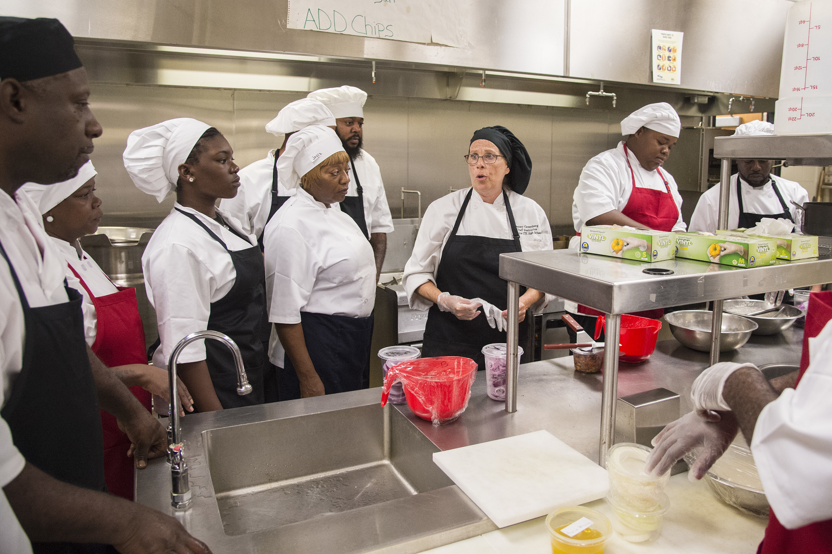 Wearing a black cap, Penny Greenberg, 62, the head of the culinary program at Dobbins Career and Technical Education High School, conducts a training program sponsored by a hospitality union UNITE Here as students gather around the stove. CLEM MURRAY / Staff Photographer