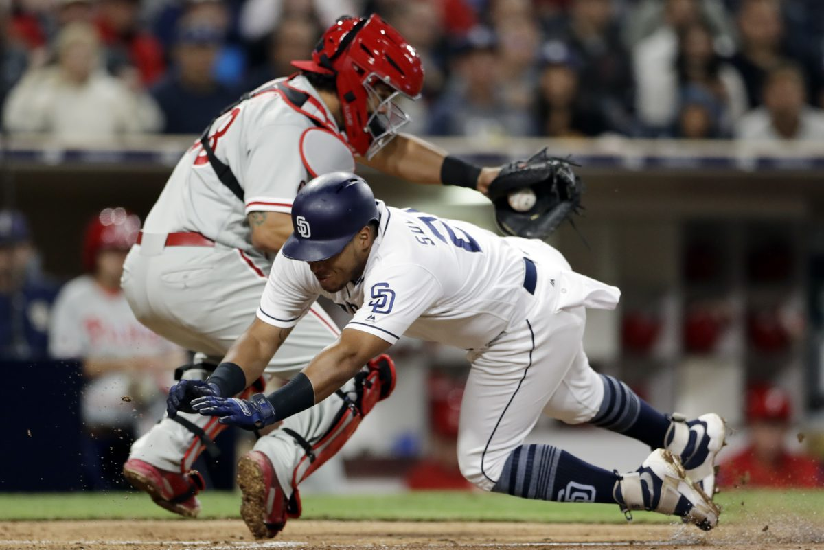 The Padres´ Yangervis Solarte dives for home, scoring from third, as Phillies catcher Jorge Alfaro gathers the throw Tuesday. The series between the teams concludes today.