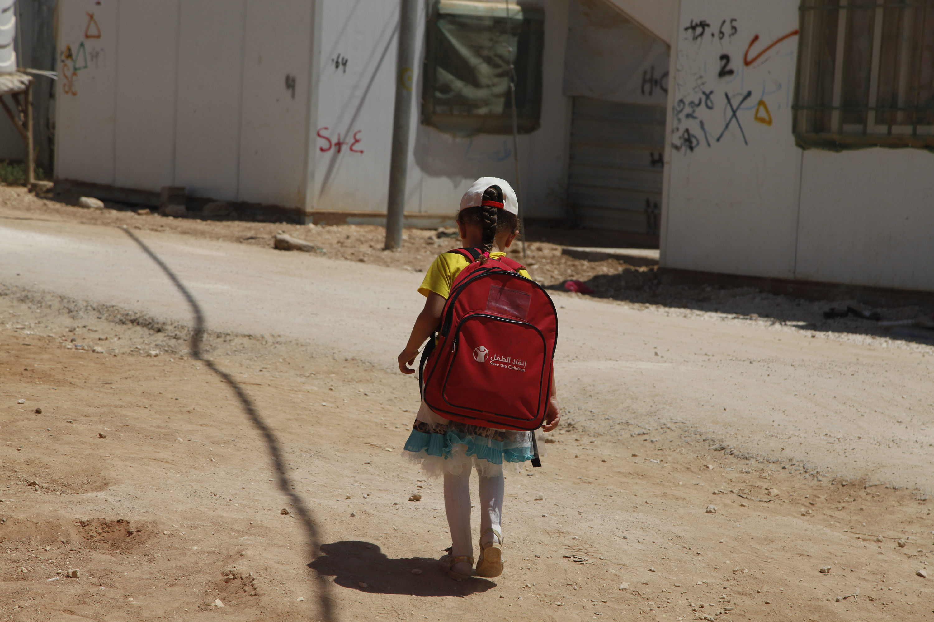 "In this Monday, Aug. 6, 2017 photo, a girl walks to school in the Zaatari Refugee Camp for Syrian refugees, in northern Jordan. More than half a million Syrian refugee children in regional host countries - Jordan, Lebanon, Turkey, Egypt and Iraq - aren't in school despite an ambitious ""no lost generation"" pledge made by donor countries at a Syria aid conference last year. The U.N. child welfare agency is trying to enroll more children in schools, but faces large funding gaps. (AP Photo/Reem Saad)"