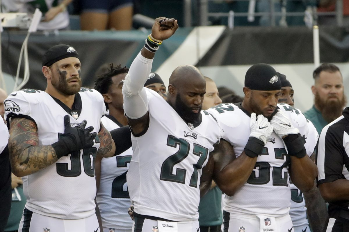 Malcolm Jenkins raised his fist during the national anthem and teammate Chris Long put his left arm around him before the team's game against the Bills on Thursday.