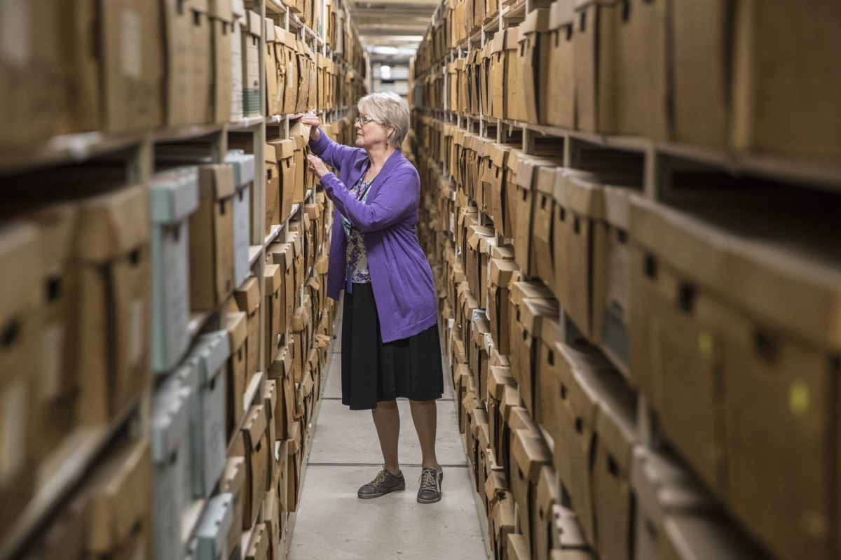 Jill Rawnsley, an archival and preservation consultant at the Philadlephia Archives, looks through some of the thousands of historical records that are part of the Achives of the city of Philadelphia. These records are just one part of many rows of records that are kept in compact shelving units in the archive.