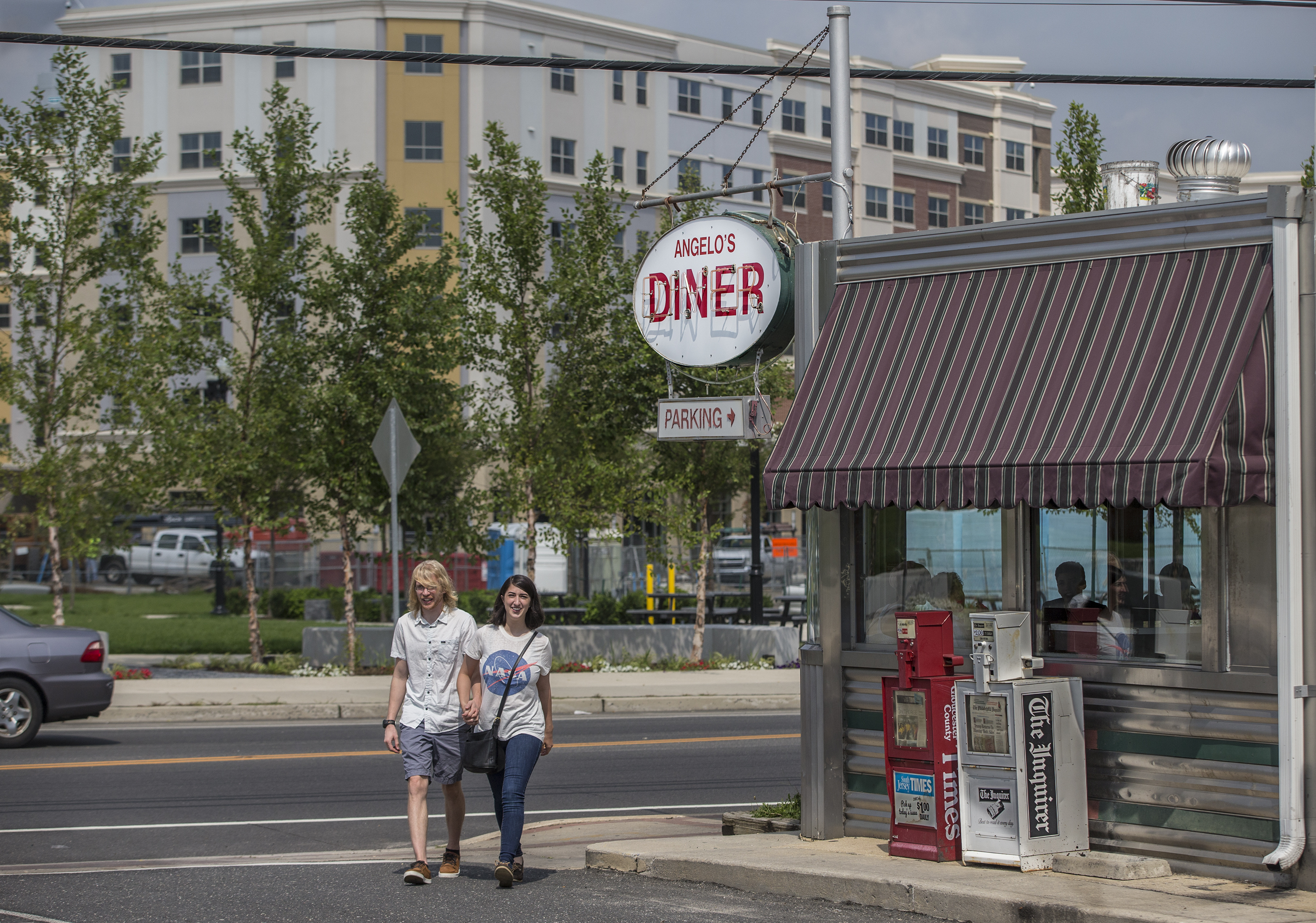 A couple walks out of Angelo's Diner, a downtown Glassboro institution with a view of the new buildings of the Rowan Boulevard project.