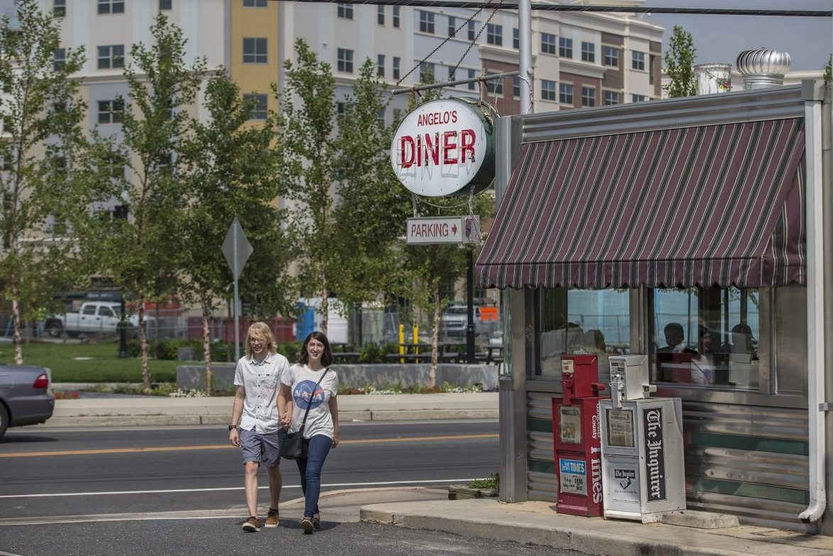A couple walks out of Angelo's, a downtown Glassboro institution with a view of the new buildings of the Rowan Boulevard project.
