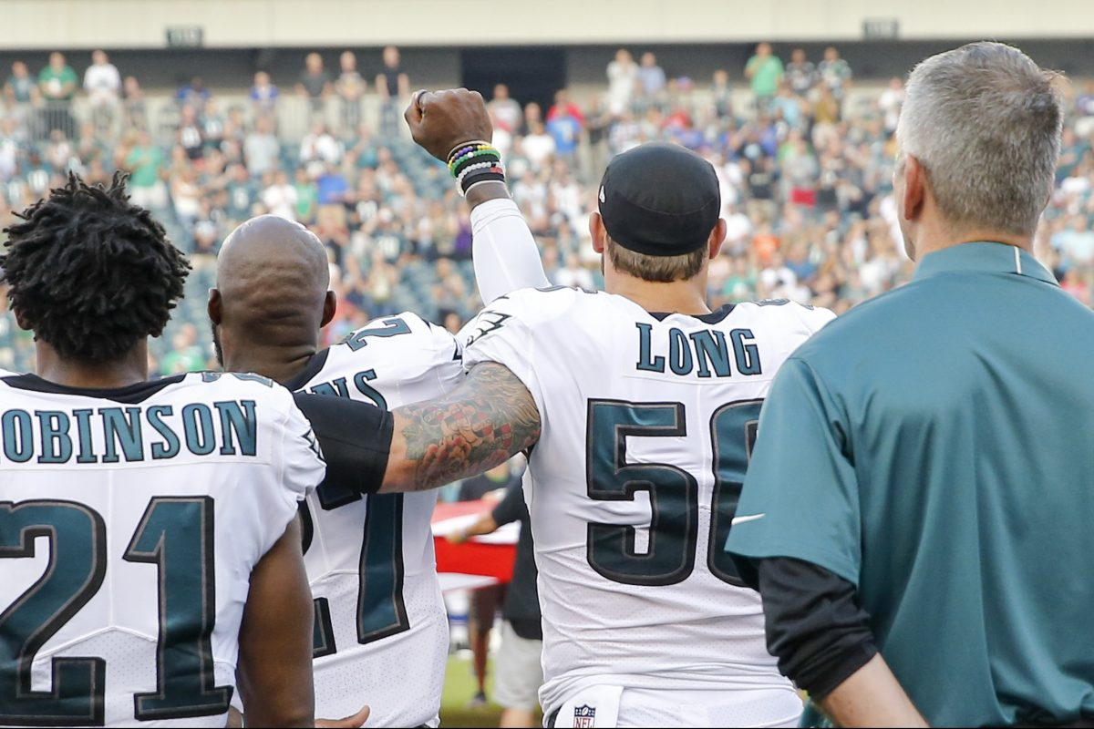 Eagles strong safety Malcolm Jenkins has his fist raised as Eagles teammate defensive end Chris Long drapes his arm around him during the national anthem Thursday night.