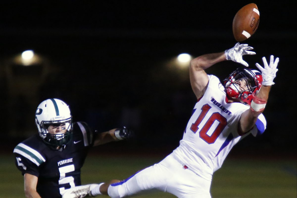 Neshaminy receiver Mike Garlick (right) tries in vain to make an acrobatic catch in a nonleague contest against Pennridge last season.