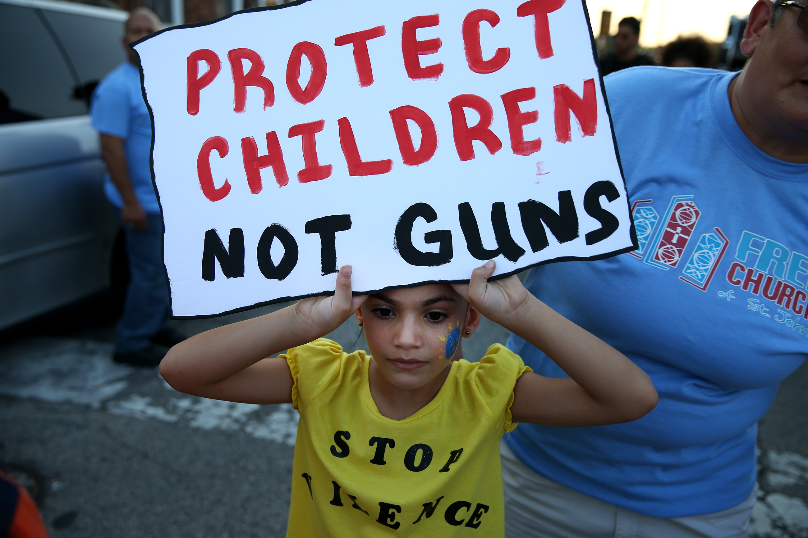 Rianna Perez, 7, a member of the Free Church of St. John, holds up a sign during the Kensington Interfaith Peace March in Philadelphia on Aug. 19, 2017. DAVID MAIALETTI / Staff Photographer