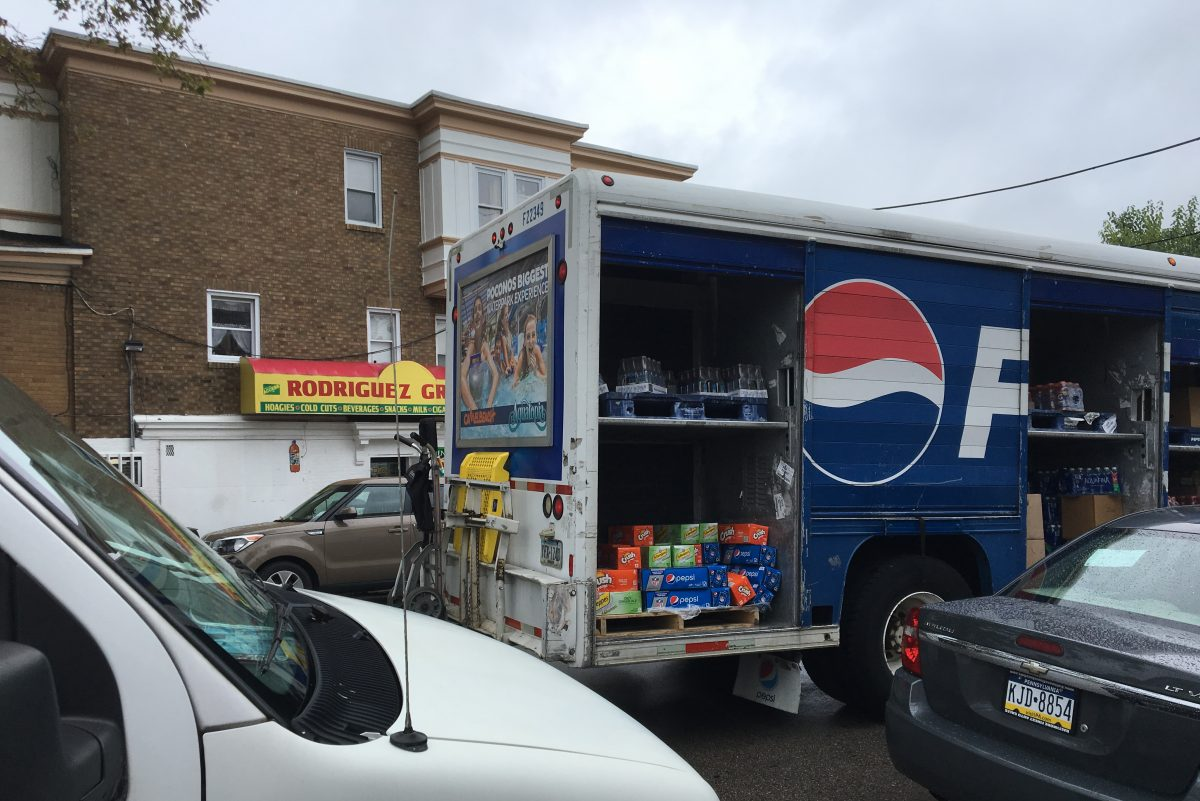 A Pepsi truck delivers soda to Rodriguez Grocery in Overbrook. The store got two deliveries per month before Philadelphia's tax on sugary drinks went into effect, said cashier Irene Rodriguez. Now, the corner store gets just one delivery per month.