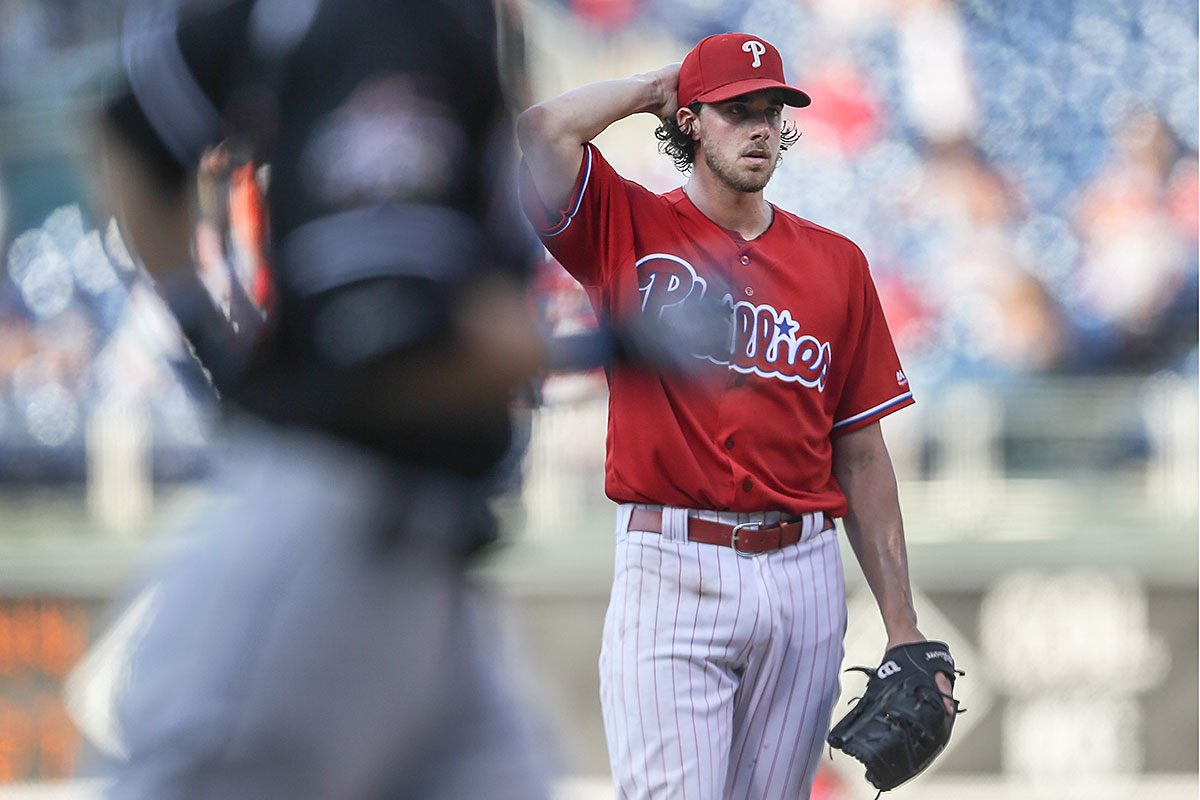 Phillies pitcher Aaron Nola reacts after the Marlins' Ichiro Suzuki rounds the bases while hitting a three-run homer in Tuesday's first game.