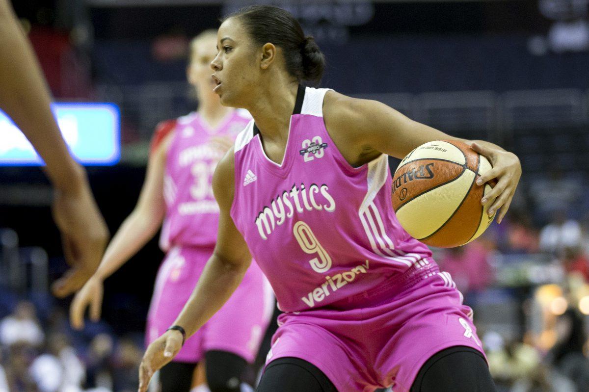 Washington Mystics guard Natasha Cloud controls the ball against the Phoenix Mercury in a WNBA game.