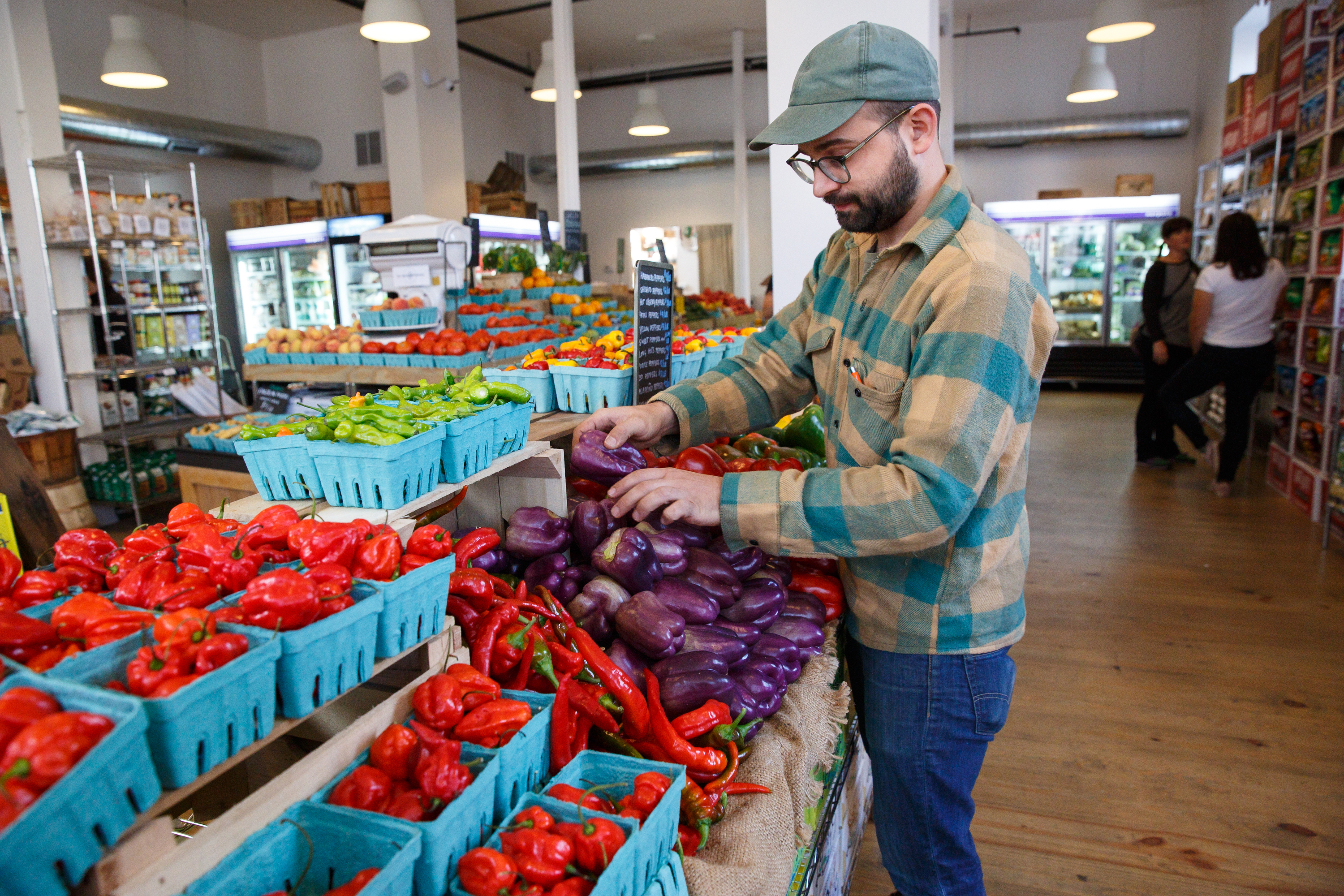 Riverwards produce Owner Vincent Finanzzo stacks produce in his store, in Philadelphia, Friday, Sept. 1, 2017. A number of shops, CSAs and delivery services that sell fresh organic produce are popping up to meet an increased demand.