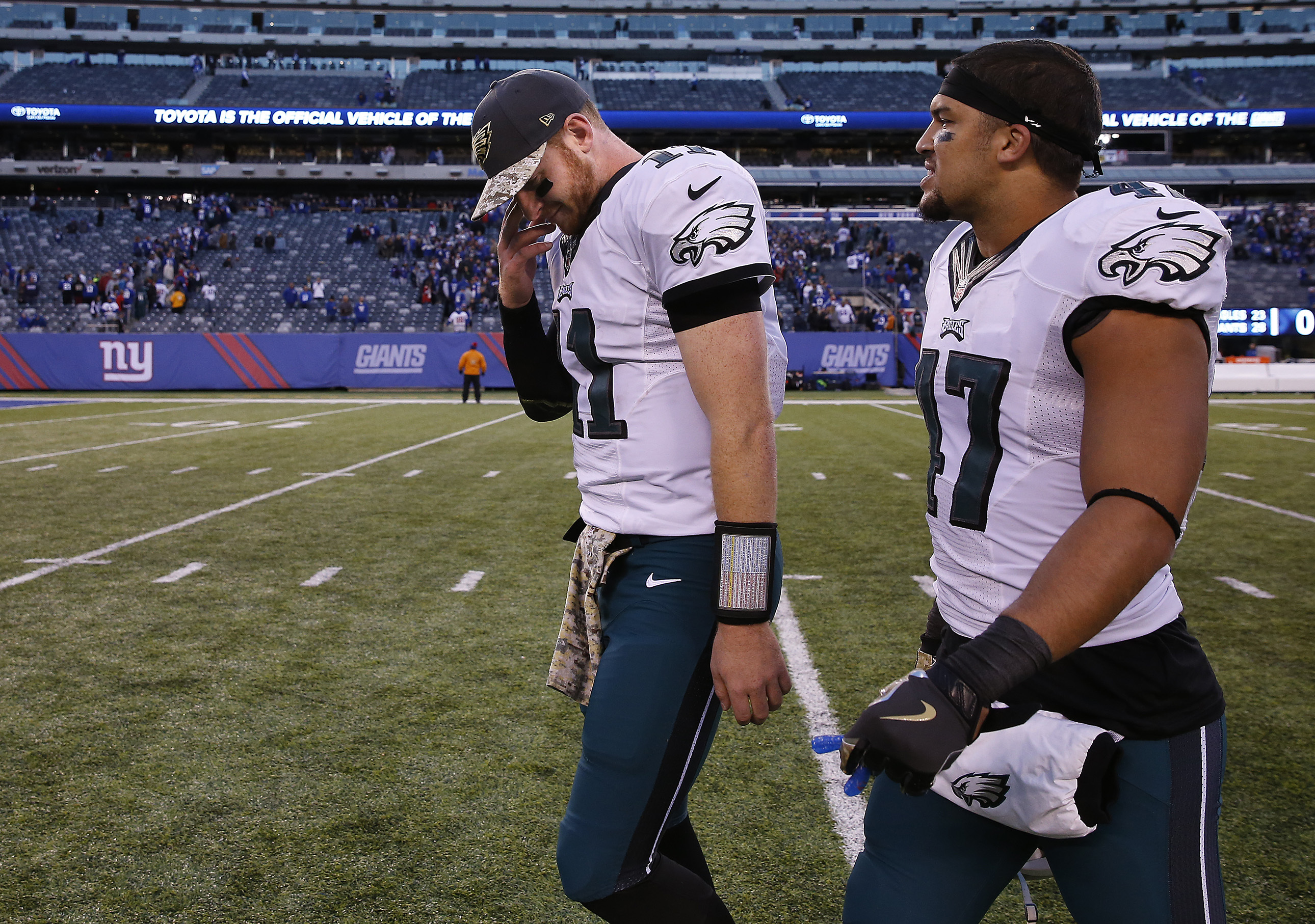 Eagles' Carson Wentz, left, and Trey Burton, right, walk off the field together after the loss to the Giants.