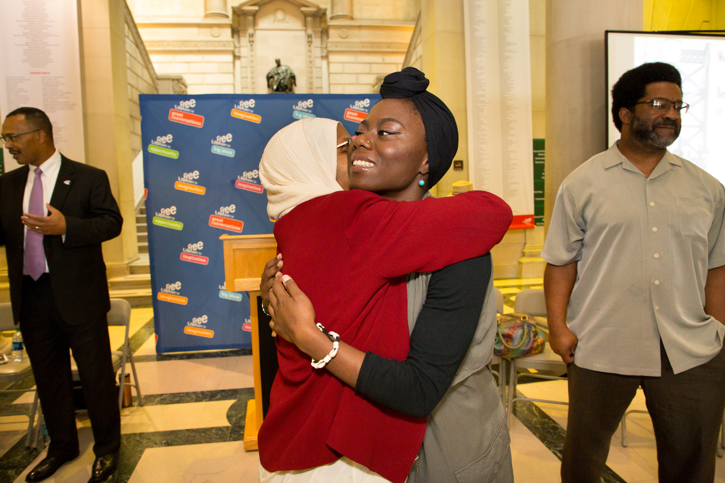 Aisha K Elmekki, left, hugs her grandaughter Husnaa Hashim, right, the new Youth Poet Laureate, after the ceremony at the Free Library, Thursday, Sept. 7, 2017.