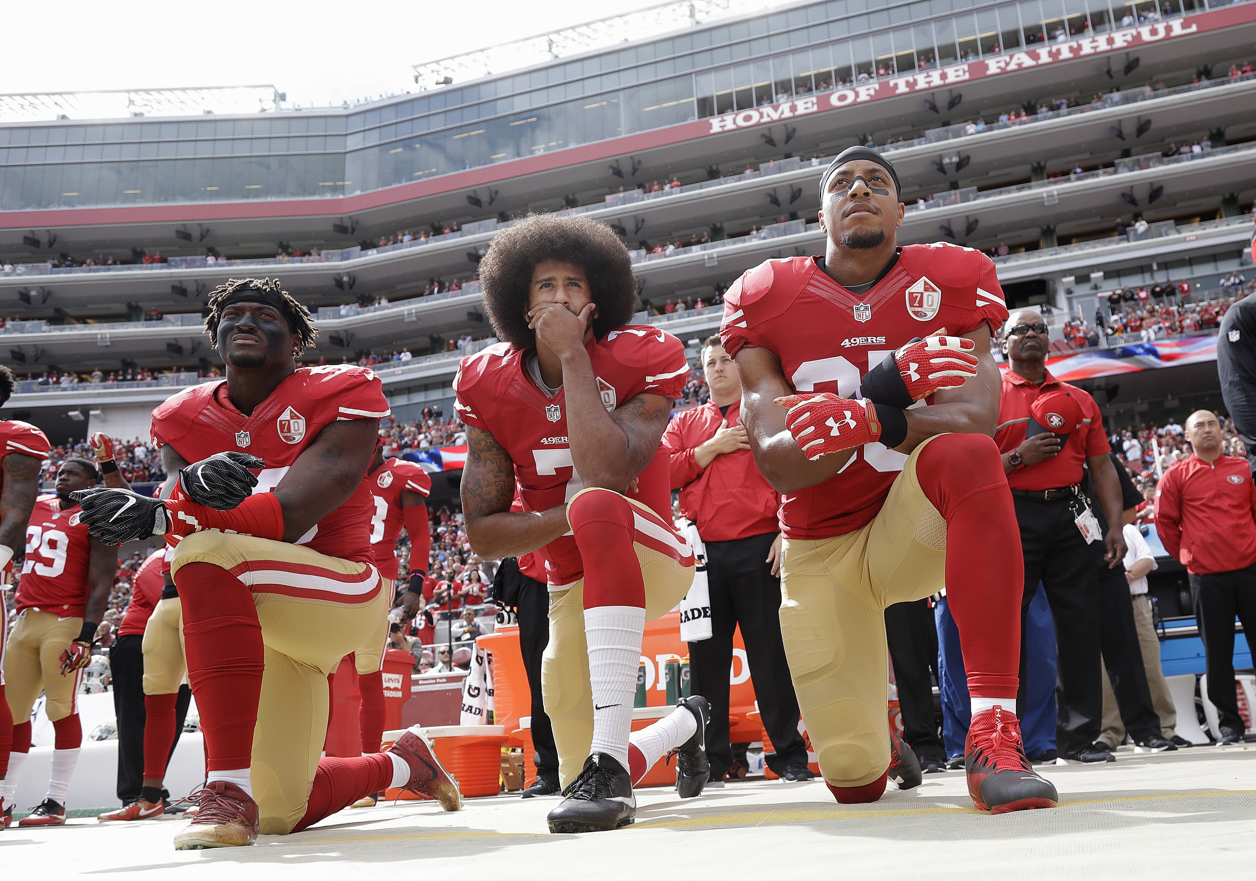 Colin Kaepernick, center, kneels with two teammates during the national anthem before the San Francisco 49ers played the Dallas Cowboys on Oct. 2, 2016.