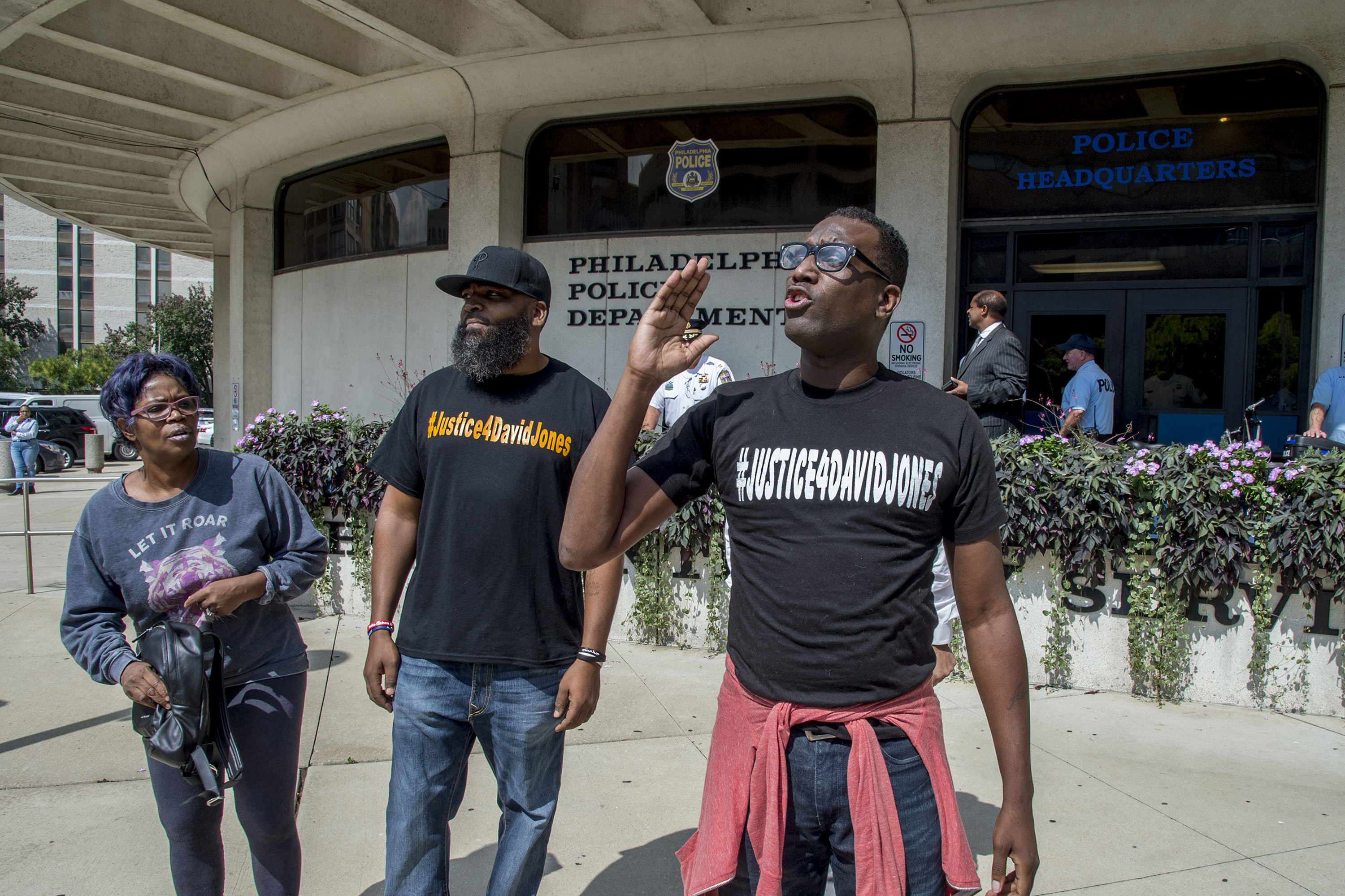Activists (from left) Rowena Faulk, Isaac Gardner, and Asa Khalif demonstrate outside Police Headquarters after the announcement of Officer Ryan Pownall´s firing.