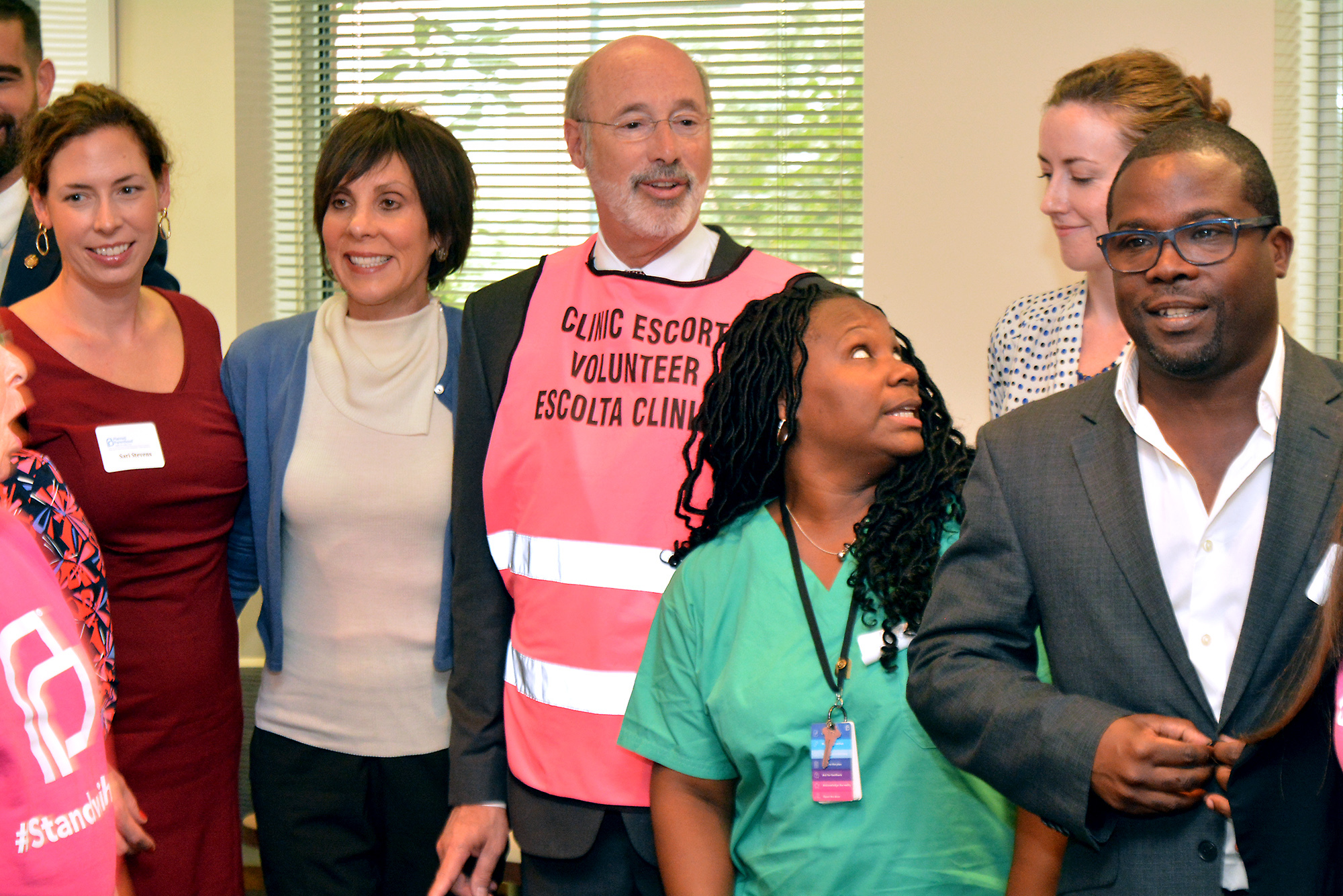 Gov. Tom Wolf, center, wears a clinic escort volunteer vest while posing for a picture with Planned Parenthood Southeastern Pa. staff, patient advocates and volunteer leaders of the Elizabeth Blackwell Health Center at Locust Street in Philadelphia.