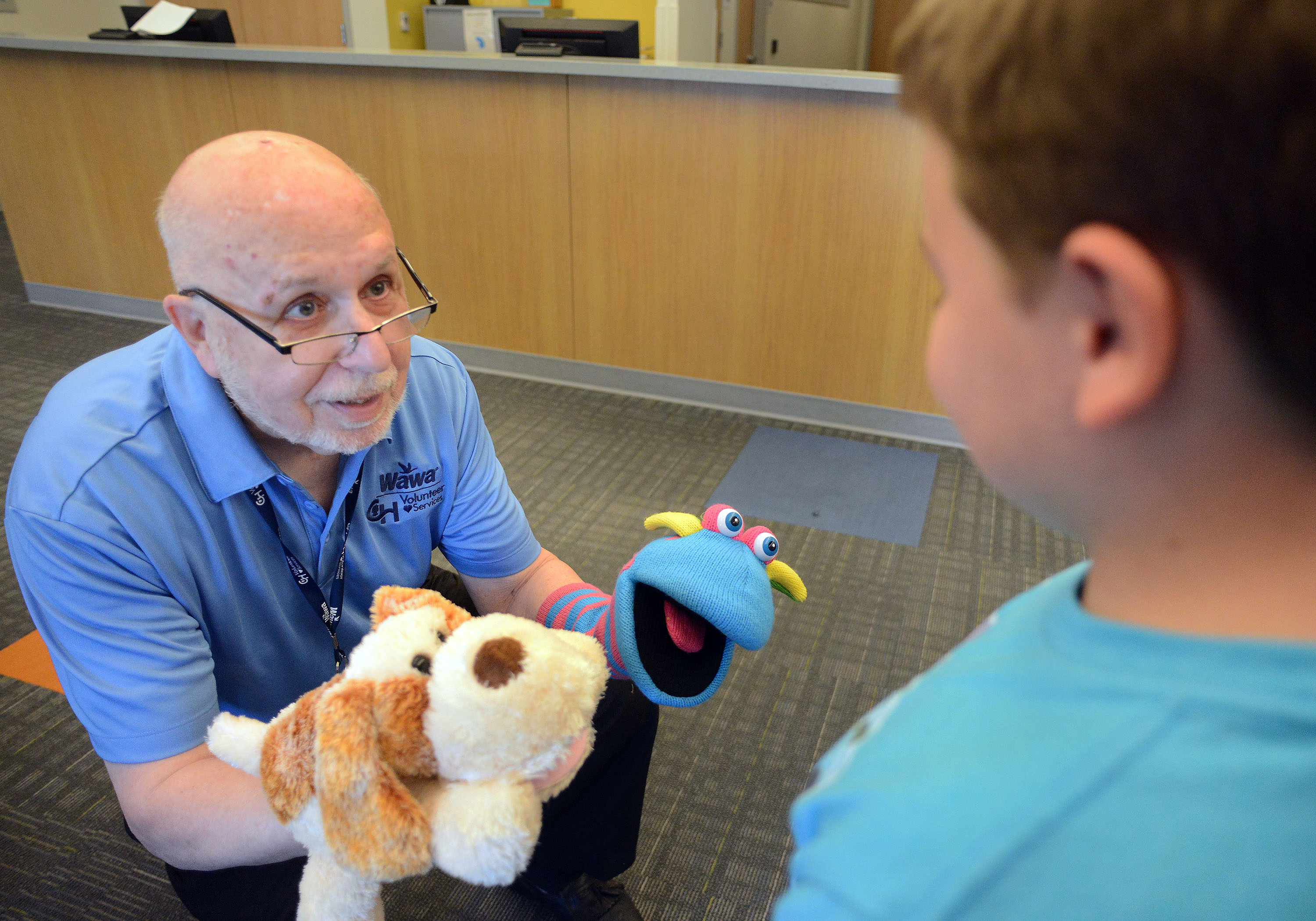 Leslie Wolff uses puppets, Rufus, left, and Blewy to talk with Jacob Taylor, 9.