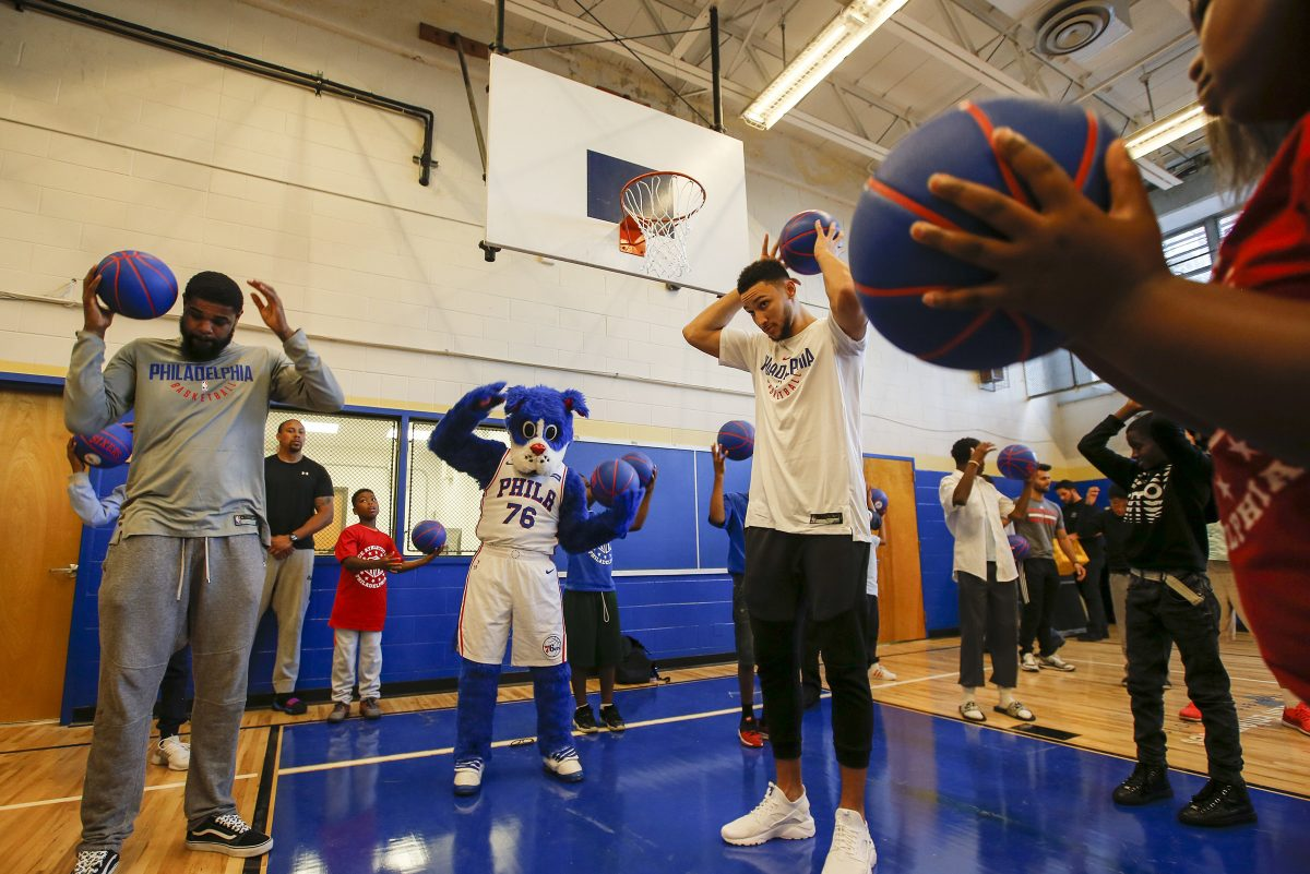 Sixers guard Ben Simmons and forward Amir Johnson warm-up with PAL participants after opening the new Strawberry Mansion PAL basketball court on Thursday.