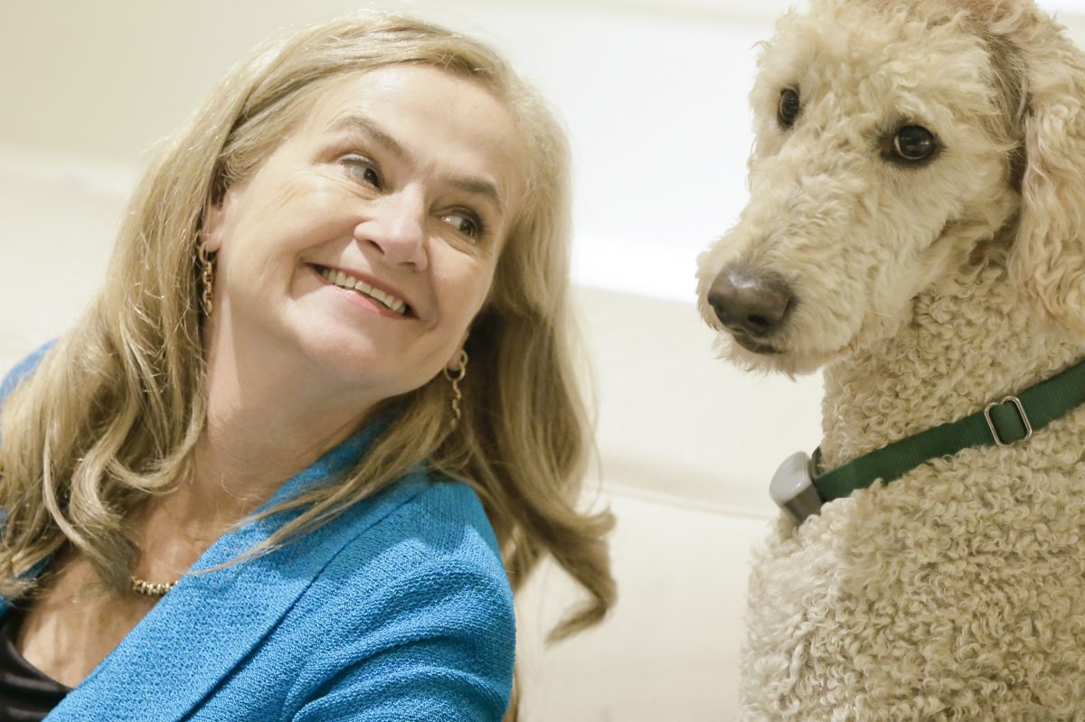 "Annie McKee, author of ""How to be Happy at Work,"" with her labradoodle, Keik."