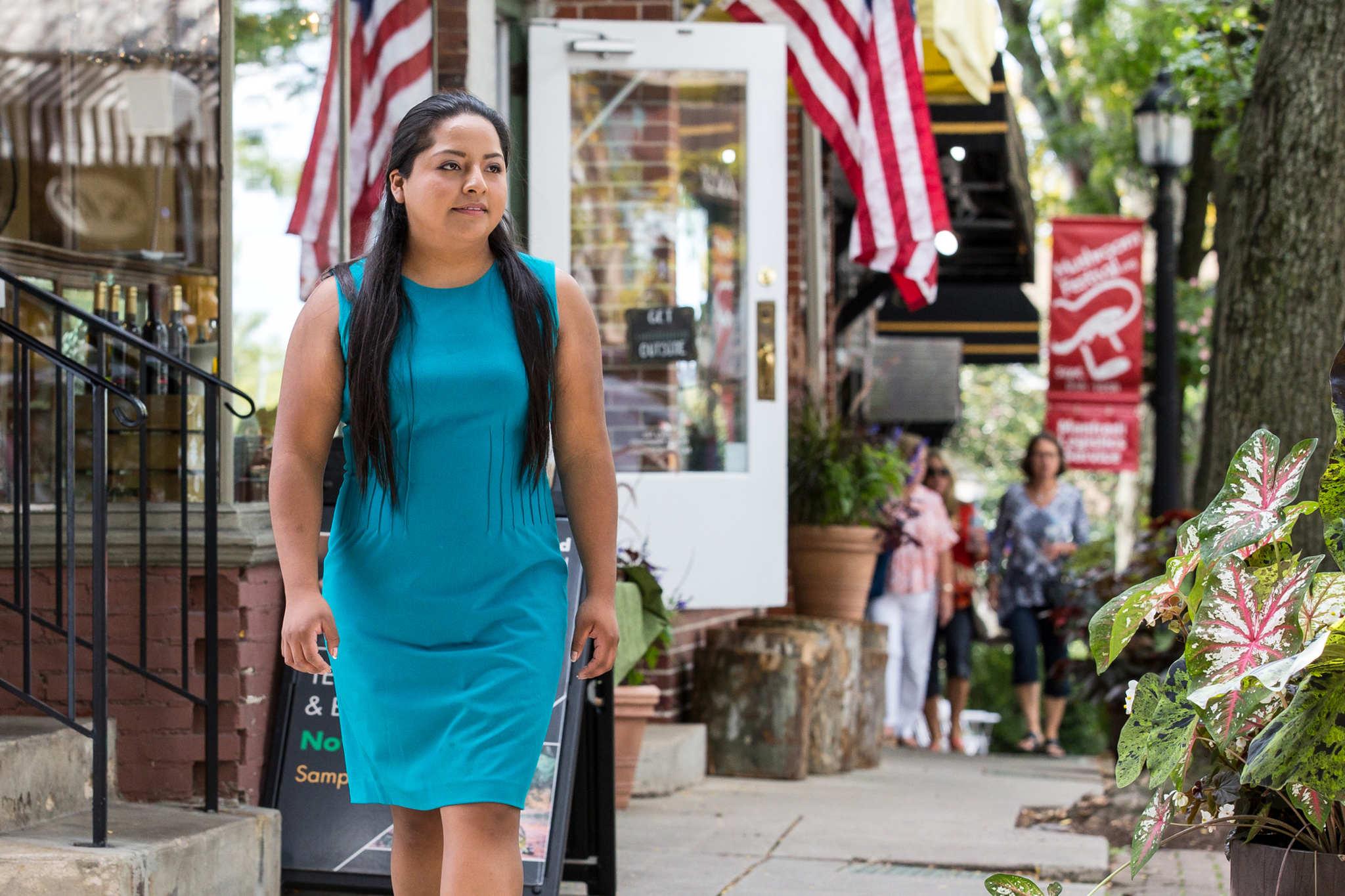 Anel Medina walks down the main street of her hometown, Kennett Square on Friday, September 8, 2017.