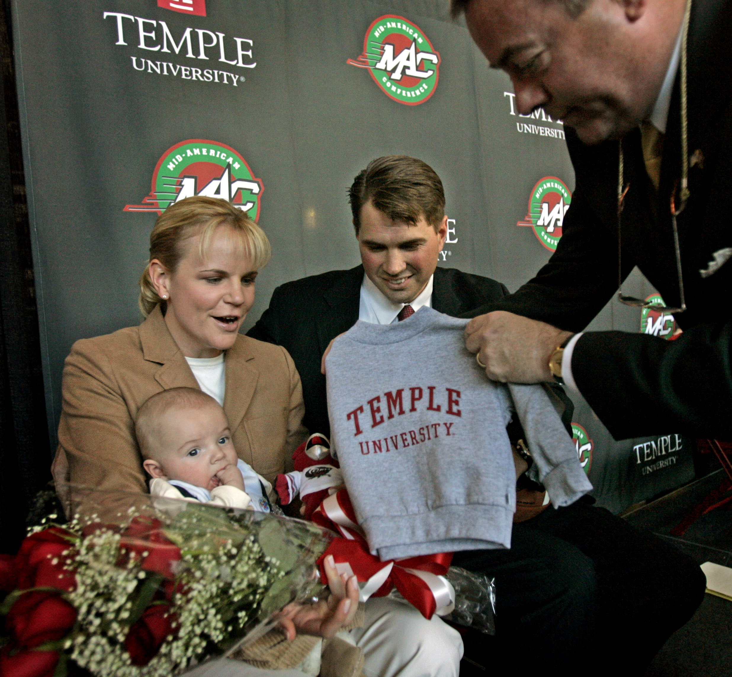 Temple AD Bill Bradshaw (right) presents gifts to new coach Al Golden, wife Kelly Elizabeth Hanna and their baby son, AJ, after Golden´s introductory press conference in December 2005.