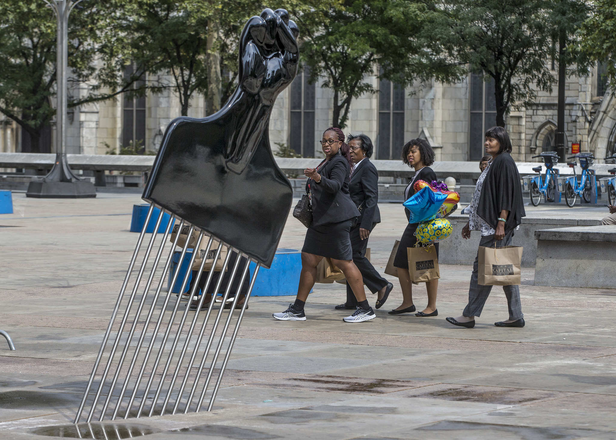"A group of women walk past the Hank Willis Thomas ""All Power to All People"" sculpture installed at Thomas Paine Plaza across from Philadelphia City Hall. The Pop Art sculpture is an Afro pick with upright fist with handled that looks like a Black Power fist."