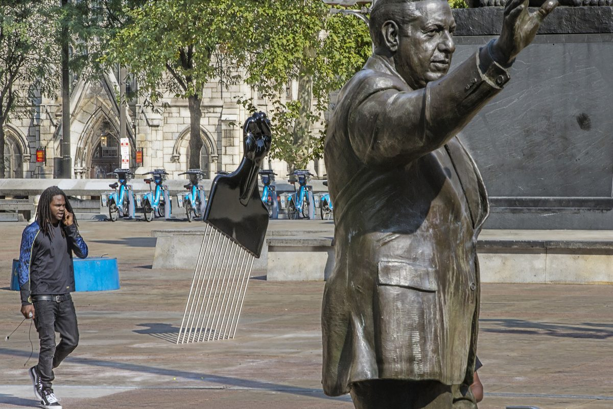 "The statue of Frank Rizzo on Thomas Paine Plaza is joined by a new sculpture called ""All Power to All People"" , a large Afro Pick with a Black Power salute as the handle was installed Tuesday September 12, 2017. The artist is Hank Willis Thomas of New York. On Tuesday at 1:30 The Mural Arts Project will add its own touch to the Rizzo statue saga with the installation a 12-foot high Afro Pick near the Rizzo statue. The Pop Art object inspired by Claes Oldenburg´s Clothespin has a Black Power Fist as its handle. The temporary installation by artist Hank Willis Thomas is the first salvo of Monument Lab a public art project kicking off Wednesday. Tuesday September 12, 2017 MICHAEL BRYANT / Staff Photographer"