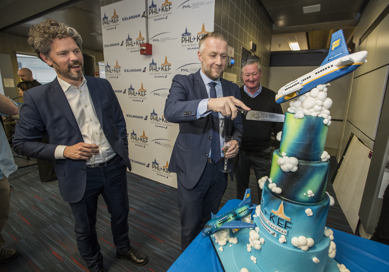 Icelandair CEO Birkir Holm Gudnason, center, cuts a cake to celebrate Icelandair's inaugural flight to Philadelphia as Reykjavik Dagur B. Eggertsson, left, and Philadelphia Mayor James Kenney, right, look on. The cake was designed by the Night Kitchen bakery in Chestnut Hill.