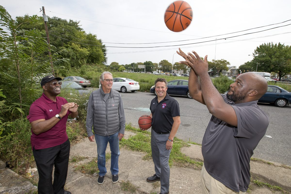 Philadelphia Youth Basketball foundation hopes basketballs will one day soar over a neighborhood that once sunk. They hope to build a basketball facility on the Logan Triangle, once home to sinking homes that had to be demoslihed. L-R: Board member and former coach Bill Ellerbee, board member John Langel, CEO and Executive DIrector Kenny Holdsman, co-founder/Program Director Eric Worley. CHARLES FOX / Staff Photographer